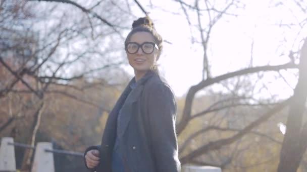 Venkovní módní portrét mladé ženy v moderní kabát, Model s dlouhými tmavými vlasy v pěkném oblečení, Pózování na ulici města. Venkovní módní koncept.