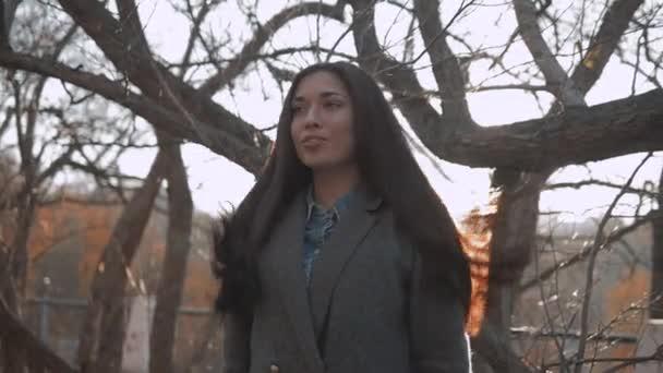 Allaperto ritratto sensuale di giovane bella donna alla moda con lunghi capelli scuri e labbra sexy che propone sulla strada di autunno. Studente ragazza bruna allaperto in cappotto.