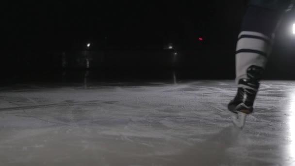 hokejista se leskne ledu na vysoké rychlosti brzdění. rozmazání pohybem. Zobrazit pouze nohy