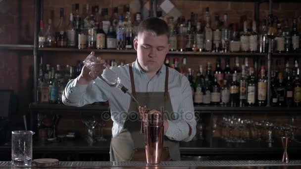Bartender pours alcoholic drink into small shaker