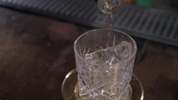 Nalil whisky koktejl do skla, zblízka. Nalévání alkoholu