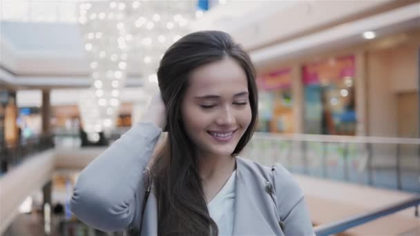 Boldog szép nő portré áll boltban. Kaukázusi a vonzó lány mosoly a nagy mall