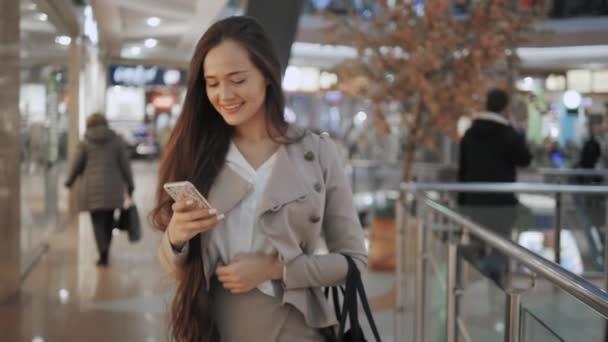 Vásárlás a nő mosolyogva beszél a telefonon, a mall táskákkal. Gyönyörű lány, smartphone, a bevásárló központ.