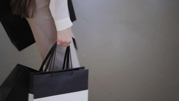 A bevásárlóközpont közelről női kéz tartja a bevásárló szatyrok