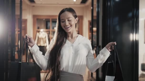 woman posing with shopping bags in mall center, elegant brunette girl show purchases in supermarket