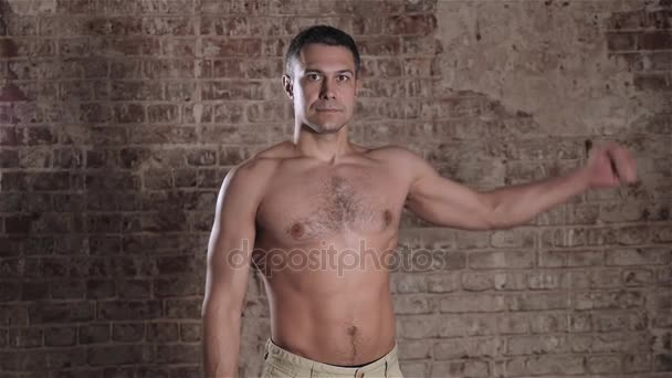 Handsome mature man with muscular topless body holding arms up. Fit businessman with biceps