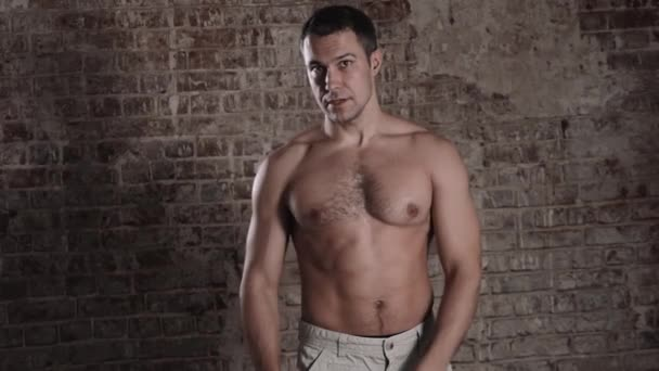 Muscular and fit mature bodybuilder posing demonstrates the core muscles. Isolated on brick background.