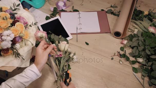 Csokor virág bolt a fából készült asztal, felülnézet kezet virágok, tabletta, rózsák és díszítő papírt, hogy férfi virágüzlet.