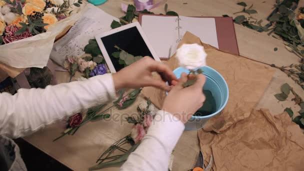 Csokor virág bolt a fából készült asztal, felülnézet kezet virágok, tabletta, rózsák és díszítő papírt, hogy férfi virágüzlet