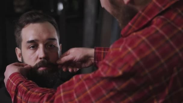 Portrait brutal bearded hipster man in the barber shop and He twists his mustache