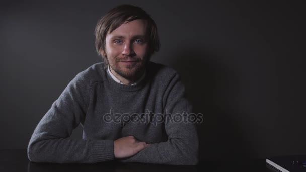 Portrét brutální vousatý muž bokové šedé pozadí. Mladý muž tvář detailní čepici