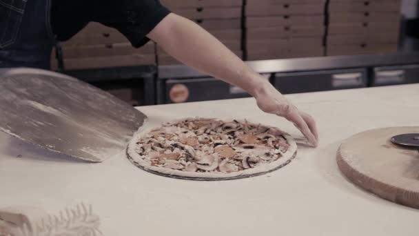 Closeup ruka kuchaře Baker v modré uniformě pizzu do trouby pro rozvoz jídel