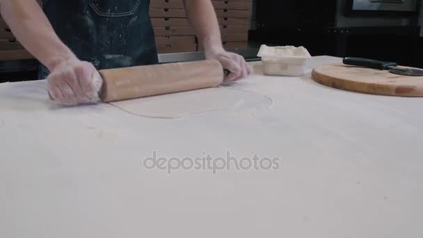 Kuchař vaření pizzu v restauraci pro dodání. Náplň pizzy s přísadami. Pohled shora. Pohled.