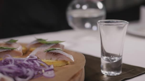 Traditional russian snacks salted herring with vegetables, onion, lemon, yellow lime, bread and shots of vodka.