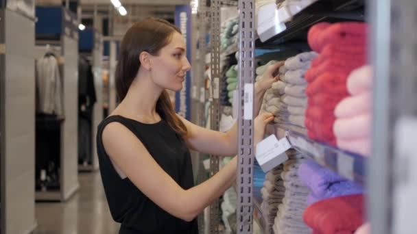 Beautiful woman inspecting and buying towels in supermarket, brunette businesswoman in shop