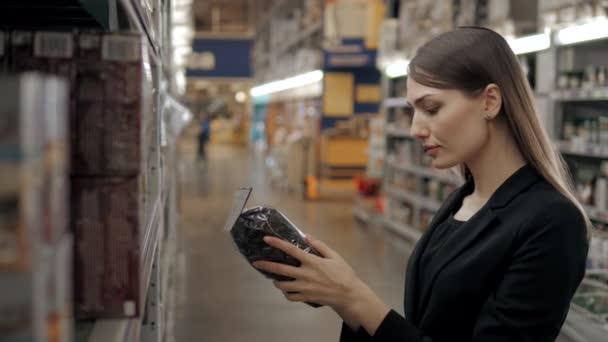 Šťastná žena zákazníků volících černý čaj v potravinách ukládat, Bruneta žen v supermarketu, nákupní