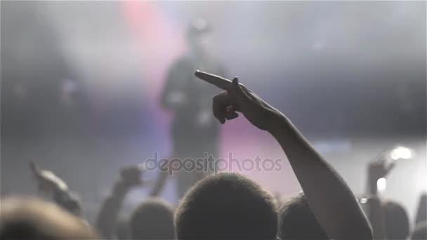 Sziluettjét az emberek feltartotta a kezét egy koncerten. Blured zenészek