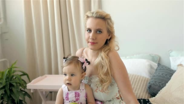 Young Mother Holding her Newborn Child. Family at home mom and child, girl with blue eyes.