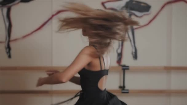 Attractive modern ballet dancer in dance studio, making pa, dance elements, warm up. Ballerina girl