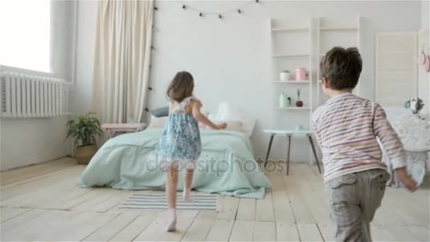 playground and kids, two little childs brother and sister run and play on bed, girl and boy hold hands together and have fun