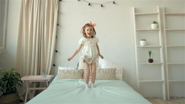 Rádi, roztomilá mladá dívka v bílých šatech baví skákání na posteli, malé usměvavé dítě