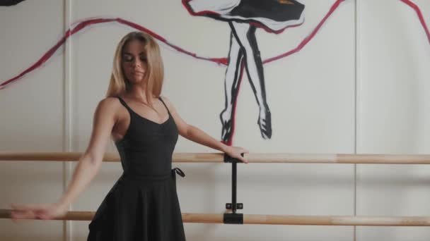 Ballerina in black outfit posing on toes in dance studio, beautiful sport girl woman
