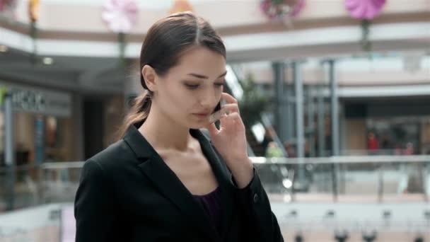 Nákupní obchodní žena mluví o telefonu v obchoďáku. Krásná dívka s smartphone v nákupním centru. Podnikatelka v kancelářské budově pracovní
