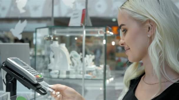 A rendelés egy bevásárlóközpontban bankkártyával fizető ügyfél. hitelkártya olvasó gép, és visszatért a bankkártya női vevői kifizetések után