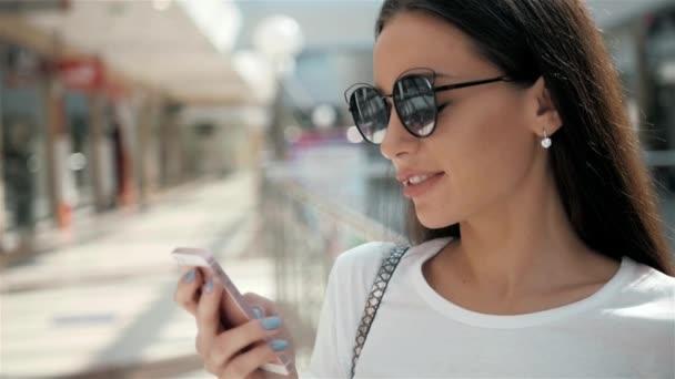 Portrét krásné mladé ženy stojící smartphone pomocí módní obchod zobrazit okno s figurínami, usmívá se nákupní tašky za slunečného dne. Spotřebitele a technologie životní styl