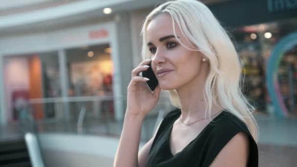 Portréja egy gyönyörű fiatal nő, egy smartphone állandó használatával egy divatház üvegablak Mindamellett, egy napsütéses napon a bevásárló szatyrok mosolyogva jeleníti meg. Fogyasztói és technológia, életmód.