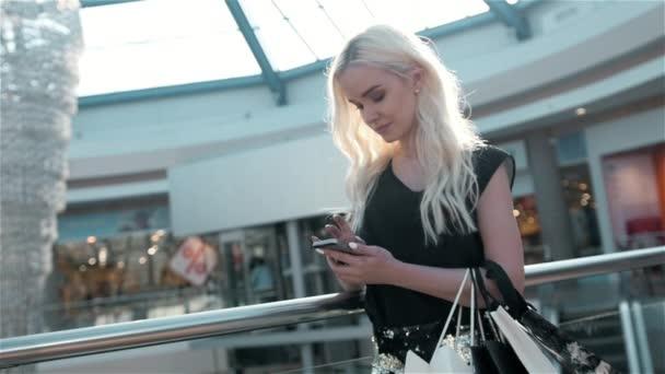 Porträt einer schönen jungen Frau, die mit einem Smartphone stehen durch ein Modegeschäft Schaufenster Glas mit Puppen, lächelnd mit Einkaufstüten an einem sonnigen Tag. Konsumenten- und Lebensstil