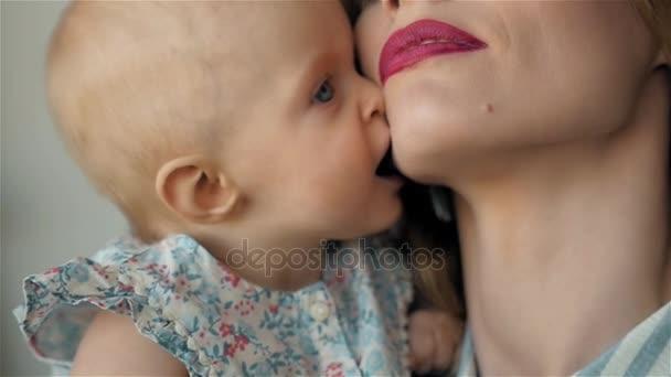 Matka a dítě líbání a objímání. Šťastná rodina ráno