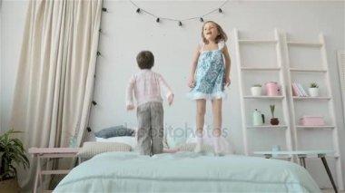 Kleine Slaapkamer Kind : Kleine jongen en meisje in pyjama hoog springen op het bed in de