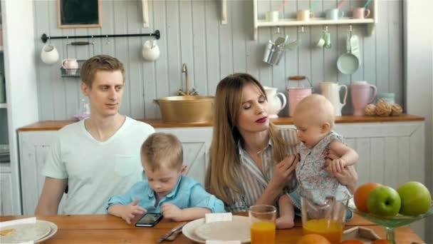 Krásné mladé rodiče a jejich děti s úsměvem v kuchyni snídani doma