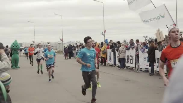 Nizhny Novgorod, Russia - May 21, 2017 Marathon male athlete crossing the finish line in park, referee judge write time