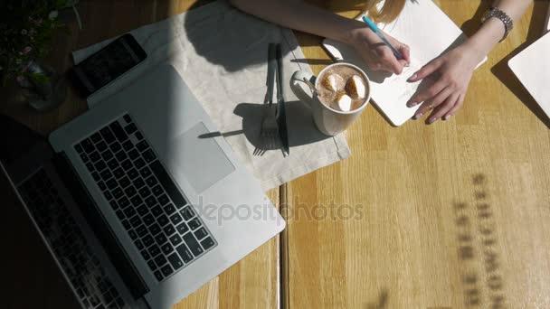 Munkaterület kézzel touch billentyűzet laptop számítógép, notebook, szendvicsek, kávézó reggelente. Felülnézet. Szabadúszó munkahelyek