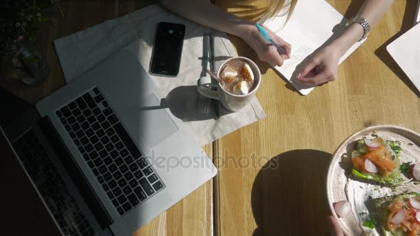 Pracovní prostor s rukou dotykové klávesnice na notebooku, notebook, sendviče v café ráno. Pohled shora. Pracoviště na volné noze