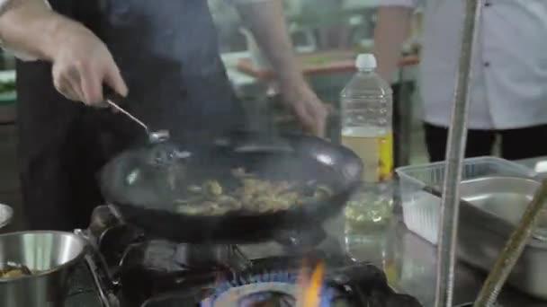 Kuchař dělá flambe omáčka na kuchyň restaurace s cibulí a vínem