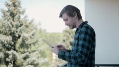 Caucasian man using an electronic tablet on the balcony of his hotel