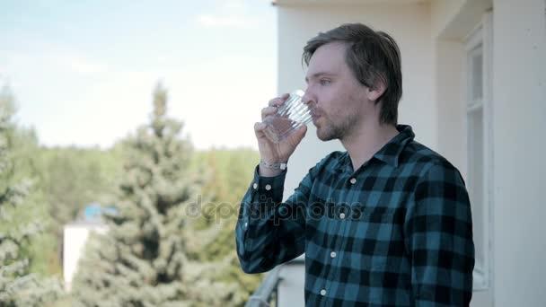 Traurige Kerl leiden Kater im Morgen und Wasser trinken