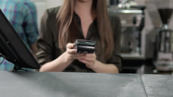 Žena číšník k načtení kreditních karet přes počítačový terminál v kavárně a zvolte
