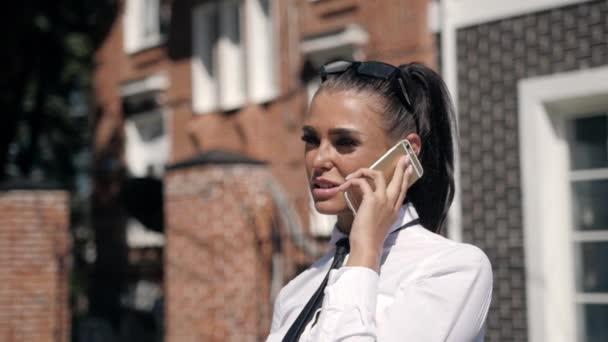 Porträt von schöne junge Geschäftsfrau draußen mit Handy, Latin Frau im Anzug in der Nähe von Hotel oder im Büro