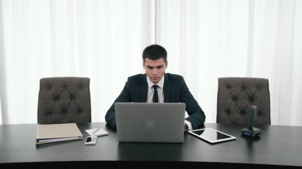 Portrait of Young handsome businessman working with laptop at desk in the modern office, with phone, unexpected obstacles, risky business, getting a second opinion from another entrepreneur