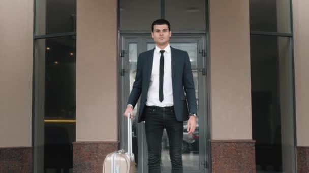 Portrét šťastný středního věku obchodník se zavazadly v hotelové hale, vážné obchodní muž s kufrem