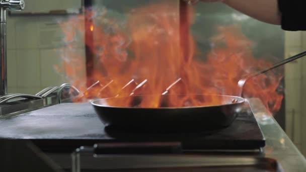 Kuchař dělá na jídlo v pánvi s velkým požárem ohněm v rybí restauraci flambe