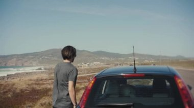 people, travel, tourism and road trip concept - happy man near rent car over ocean landscape gets into the car, tourist traveller