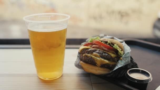 Detailní záběr velké chutné dvojitý hamburger, rajčata hovězí a pivo