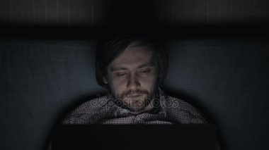 Tired young man sleeping and keeping one hand above head, lying on bed near laptop, man overworked at night
