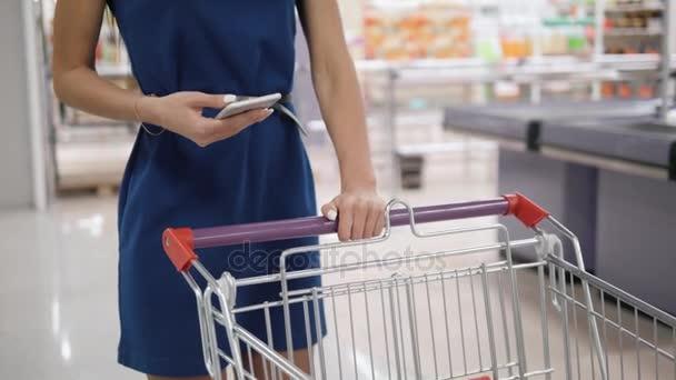 Žena používající mobilní telefon při nakupování v supermarketu, vozík mall supermarket obchod