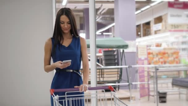 Woman using mobile phone while shopping in supermarket, trolley mall grocery shop store